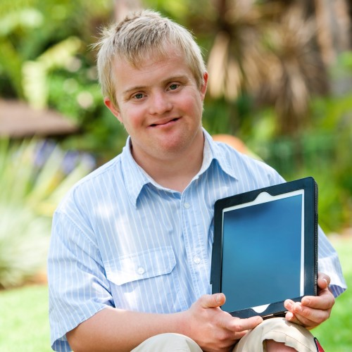 Close up portrait of disabled boy holding blank tablet with copy space outdoors.